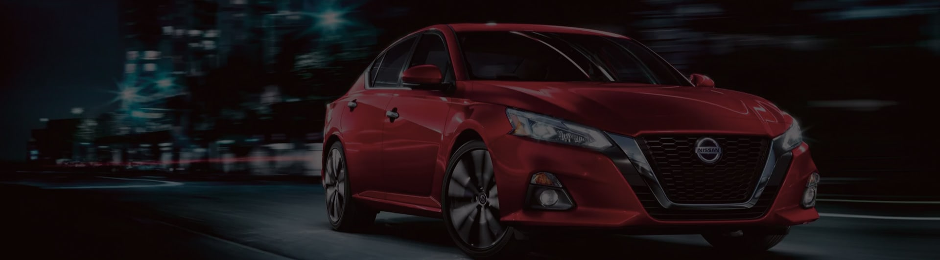 Red Nissan Altima driving through city at night